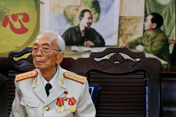 Gen. Vo Nguyen Giap stands in front of a painting of himself and Vietnamese President Ho Chi Minh